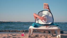 Mädchen, das auf dem Strand liegt und ein Buch liest stock footage