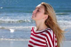 Mädchen, das auf dem Strand sich entspannt Stockfotos