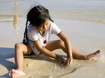 Mädchen, das auf dem Strand spielt Lizenzfreies Stockfoto