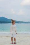 Mädchen, das auf dem Strand und den Blicken in den Abstand steht Stockfotos