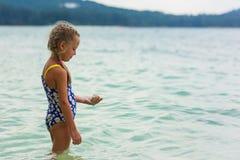 Mädchen, das auf dem Strand und den Blicken in den Abstand steht Stockfoto