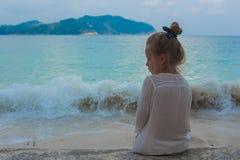 Mädchen, das auf dem Strand und den Blicken in den Abstand steht Lizenzfreie Stockfotos