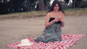 Mädchen, das auf dem Strand, unter Verwendung des Handys und des Lachens sitzt stock footage