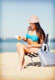 Mädchen, das auf dem Strandstuhl ein Sonnenbad nimmt Stockfotografie