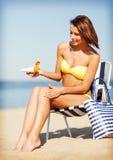 Mädchen, das auf dem Strandstuhl ein Sonnenbad nimmt Stockbild