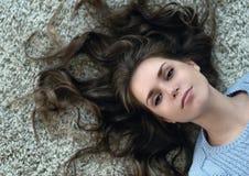 Mädchen, das auf dem Teppich mit ihrem Haar betrachtet die Kamera liegt lizenzfreie stockfotos
