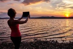 Mädchen, das auf dem Tisch den Sonnenuntergang fotografiert Lizenzfreies Stockbild