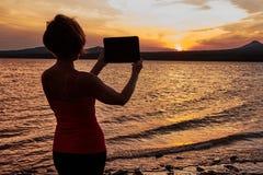 Mädchen, das auf dem Tisch den Sonnenuntergang fotografiert Lizenzfreie Stockfotografie