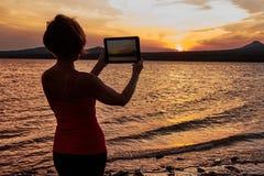Mädchen, das auf dem Tisch den Sonnenuntergang fotografiert Lizenzfreies Stockfoto