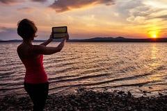 Mädchen, das auf dem Tisch den Sonnenuntergang fotografiert Stockbilder