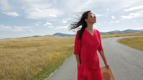 Mädchen, das auf dem Weg auf einem Gebiet zu den Bergen in einem roten Kleid geht stock footage