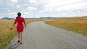 Mädchen, das auf dem Weg auf einem Gebiet zu den Bergen in einem roten Kleid geht stock video
