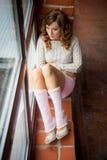 Mädchen, das auf dem Windowsill sitzt Beschneidungspfad eingeschlossen lizenzfreies stockbild