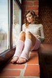 Mädchen, das auf dem Windowsill sitzt Beschneidungspfad eingeschlossen stockfoto