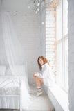 Mädchen, das auf dem Windowsill sitzt Beschneidungspfad eingeschlossen lizenzfreies stockfoto