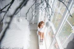 Mädchen, das auf dem Windowsill sitzt Beschneidungspfad eingeschlossen lizenzfreie stockfotos