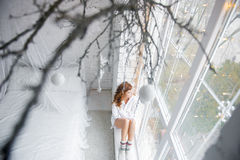 Mädchen, das auf dem Windowsill sitzt Beschneidungspfad eingeschlossen stockbilder