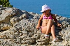 Mädchen, das auf den Felsen durch das Meer sitzt Stockbild