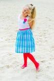Mädchen, das auf den sandigen Strand geht Lizenzfreie Stockbilder