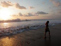 Mädchen, das auf den Strandsonnenuntergang geht Lizenzfreies Stockbild