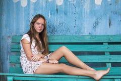 Mädchen, das auf der Bank, alte schmutzige Wand auf dem Hintergrund sitzt Stockbild