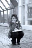 Mädchen, das auf der Brücke sitzt Stockfoto