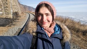 Mädchen, das auf der Circum-Baikal-Eisenbahn im Winter wandert Warm angekleidet - Schal und Hut gestrickt, warmer Mantel stockfotos