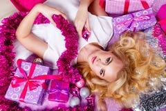 Mädchen, das auf der Couch liegt Um Geschenke und festliches Lametta Lizenzfreies Stockbild