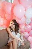 Mädchen, das auf der Couch mit vielen Ballonen sitzt Lizenzfreie Stockfotografie