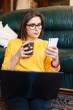 Mädchen, das auf der Couch unter Verwendung der modernen Technologie sitzt Lizenzfreies Stockfoto