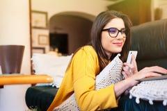 Mädchen, das auf der Couch unter Verwendung der modernen Technologie sitzt Lizenzfreie Stockbilder
