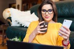 Mädchen, das auf der Couch unter Verwendung der modernen Technologie sitzt Lizenzfreie Stockfotos