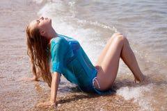 Mädchen, das auf der Küste sitzt Stockfotografie