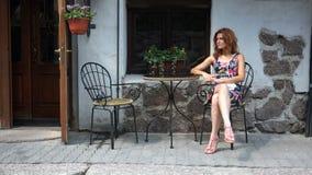 Mädchen, das auf der Kamera sitzt an einem Tisch außerhalb eines Cafés aufwirft stock video footage