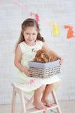 Mädchen, das auf der Leiter mit einem Kaninchen sitzt Lizenzfreie Stockbilder
