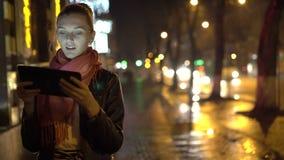 Mädchen, das auf der Pflasterung, unter Verwendung der Tablette auf der Nacht steht 4K stock footage
