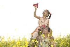 Mädchen, das auf der Schulter und dem werfenden Papierflugzeug des Vaters sitzt stockfotografie