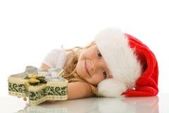 Mädchen, das auf der Tabelle mit Weihnachtskasten sich lehnt Lizenzfreie Stockfotografie