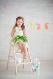 Mädchen, das auf der Treppe mit Tulpen sitzt Lizenzfreie Stockfotografie