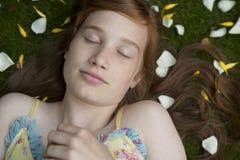 Mädchen, das auf die Blumenblatt-Augen geschlossen legt Stockbild