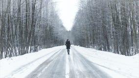 Mädchen, das auf die Straße zum Winterholz geht stock footage