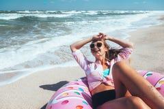 Mädchen, das auf Donut lilo auf dem Strand sich entspannt stockbilder