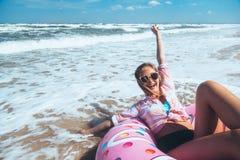 Mädchen, das auf Donut lilo auf dem Strand sich entspannt lizenzfreies stockfoto
