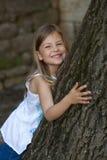 Mädchen, das auf Eichenbaum sich lehnt Lizenzfreie Stockfotos