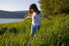 Mädchen, das auf ein LOGON-hohes Gras geht Stockbild