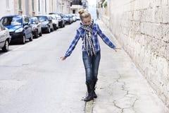 Mädchen, das auf eine Stadtstraße geht Lizenzfreie Stockbilder