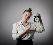 Mädchen, das auf eine Uhr zeigt Lizenzfreies Stockfoto