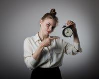 Mädchen, das auf eine Uhr zeigt Lizenzfreie Stockbilder