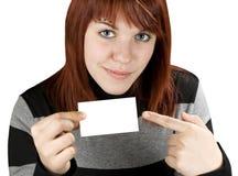 Mädchen, das auf eine unbelegte Visitenkarte zeigt Stockfoto