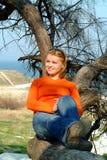 Mädchen, das auf einem Baum sich entspannt Stockbild
